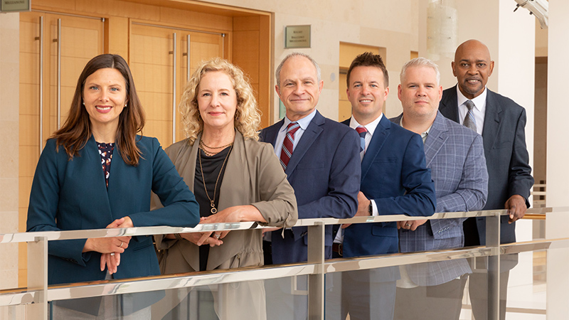 Overture's six executive leaders standing against a railing